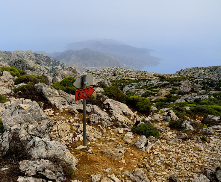Turistický smerovník na planinu Lastos, v pozadí výhľady z vrcholu Kali Limni